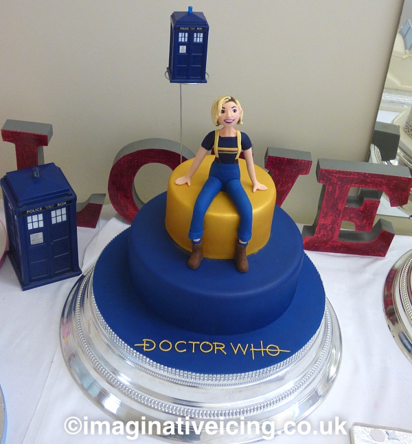 Doctor Who 13th Doctor Regeneration / Birthday Cake - with icing model of Jodie Whittaker 2018 - the word Love in the background