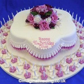 Pretty Posy Petal shaped 90th Birthday Cake with pink frills & 90 candles