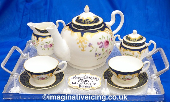 Cake shaped as a Teapot with icing Cups and saucers, Milk Jug and sugar bowl on a silver cake board made to look like a silver tray