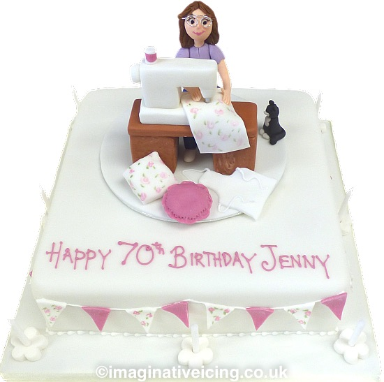 Sewing Machine Birthday Cake - Square cake iced in white with icing model of a lady sewing flowery material on a sewing machine. A tiny black cat sat at her side. Piped inscription on top of the cake. Edible bunting round the sides of the cake, candles on board.