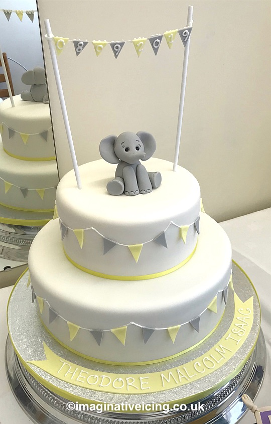 Round 2 tier Baby Elephant Christening Cake - Naming Day. iced in White with Lemon and pale grey bunting. Date Piped in icing on edible bunting draped between poles, name piped in icing on icing banner on cake board.  Edible bunting round sides of cake trimmed with lemon yellow ribbon. Displayed on Silver base stand.