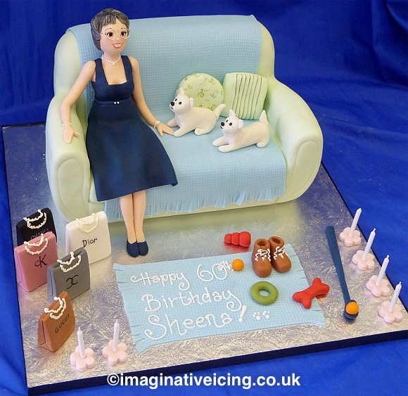 Cake shaped as a Sofa with icing model of Birthday lady in cocktail dress & pearl necklace wearing glasses. Icing Models of small white dogs, chew toys, walking boots and shopping bags of designer brands. Inscription piped on icing rug.
