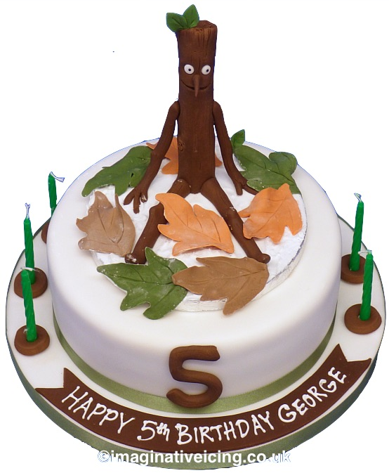 Stickman Birthday Cake, Icing model of Stickman with Autumn leaves on top of a round cake iced in white. icing number at the front with green candles on iced board. green ribbon round cake and cakeboard.