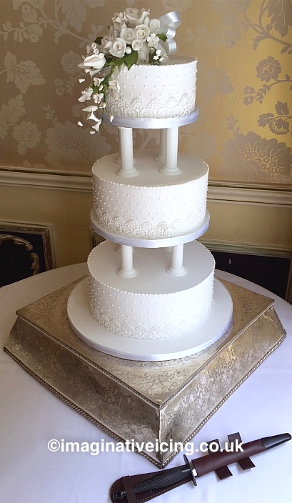 Classic Three Tiered Royal Iced Wedding Cake on pillars with Icing flowers on top tier and delicate piped detail on sides. Lace ribbon round base of each tier.