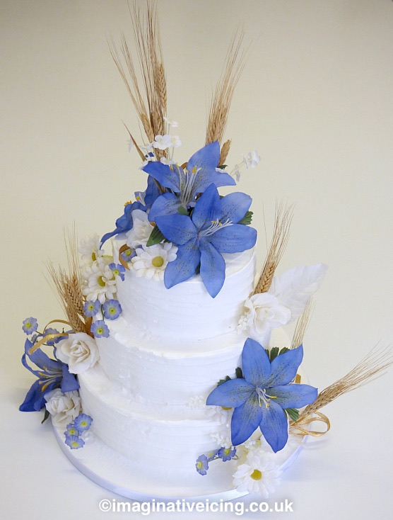 Rural Countryside Rustic Royal iced Wedding Cake - Ears of corn & flowers, daisies, large lilies, small blossoms, loops of golden ribbon.