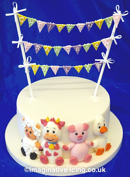 Baby Farm Animals Christening / Naming Day Bunting Cake. Lamb, calf, Piglet, Duckling. Inscription piped on edible bunting hung on ribbon between two poles with ribbon bows. Cake iced in white.