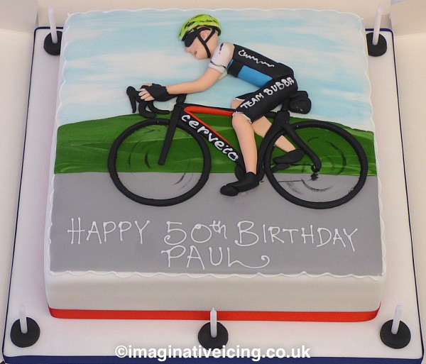 Road Cyclist 50th Birthday Cake - square cake iced in white with a icing bicycle and rider modelled in relief on top of the cake. road, green hills and blue sky. inscription piped in royal icing on road. Candles on board. clothing, logos and type of bike can be altered to suit the birthday person.
