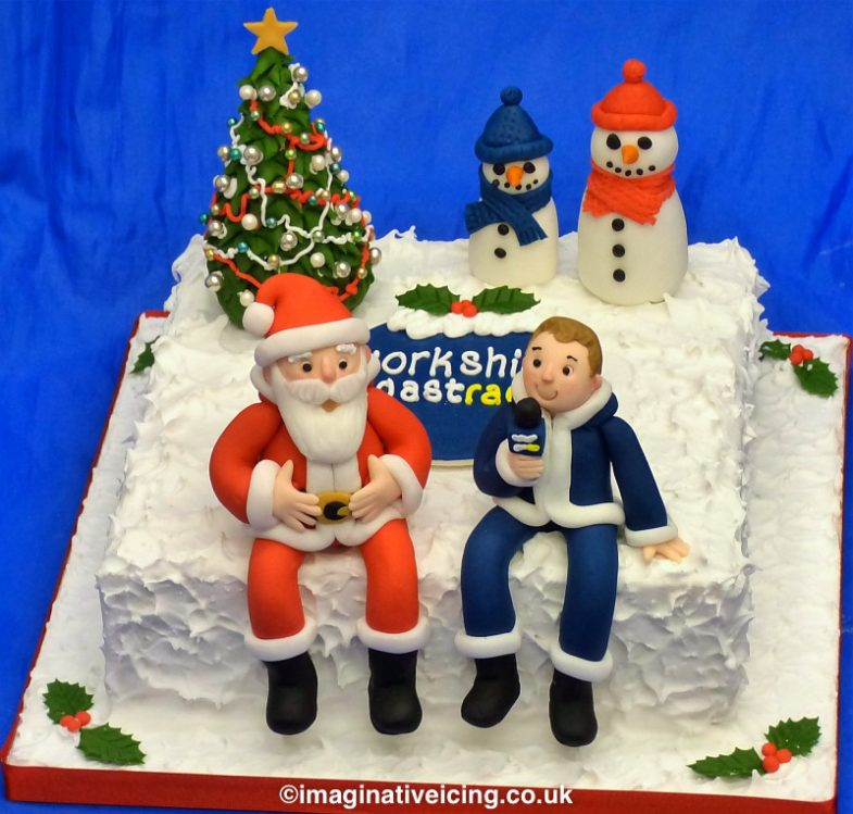 Christmas Cake with icing models.   2 snowmen look on as Local Radio Breakfast DJ Paddy Billington of Yorkshire Coast Radio interviews Father Christmas on the radio before he sets off to deliver the Christmas presents from the north Pole.