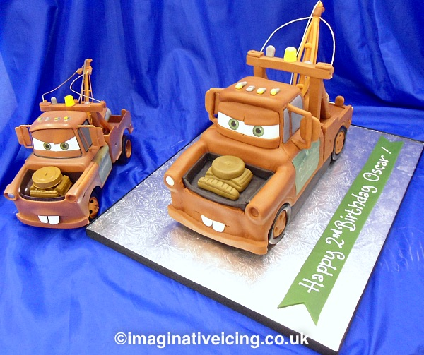3D Tow Truck shaped birthday cake - Mater from the movie Cars This cake was shaped to look like the birthday boys' favourite toy vehicle which is seen here on the left of the image.. the cake is the one on the silver board.