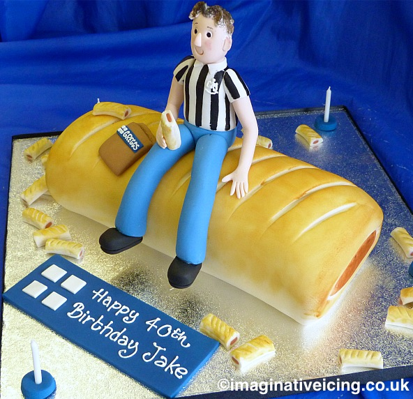 Greggs Sausage Roll shaped Birthday Cake with icing model of the birthday person eating a sausage roll.