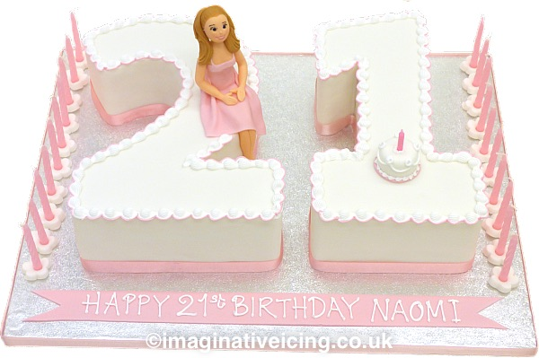 """21st birthday cake numbers - """"Pretty in Pink"""" cake numerals iced in white with piped edge, pink ribbon round the base. Icing figure of the birthday girl in a party dress and a mini icing birthday cake with a candle on top of cakes. 21 candles on silver board with piped inscription on a pink icing banner. Board edge trimmed with pink ribbon.   Although seen in pink here as cake was for a girl who liked this colour,  the colour theme can be changed to suit. Figure can be boy or girl and dressed in other clothing, jeans & t-shirt, football kit or sports wear perhaps?"""