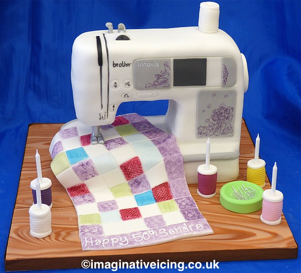 Sewing Machine Birthday cake - 3d shaped birthday cake made to look similar to the birthday person's own sewing machine. Sewing an Icing Quilt. candles stood in edible cotton reels. Inscription piped in icing on quilt. edible needles and pins in an icing container. Cake board iced to look like a wooden work top. Trimmed with ribbon round board edge.