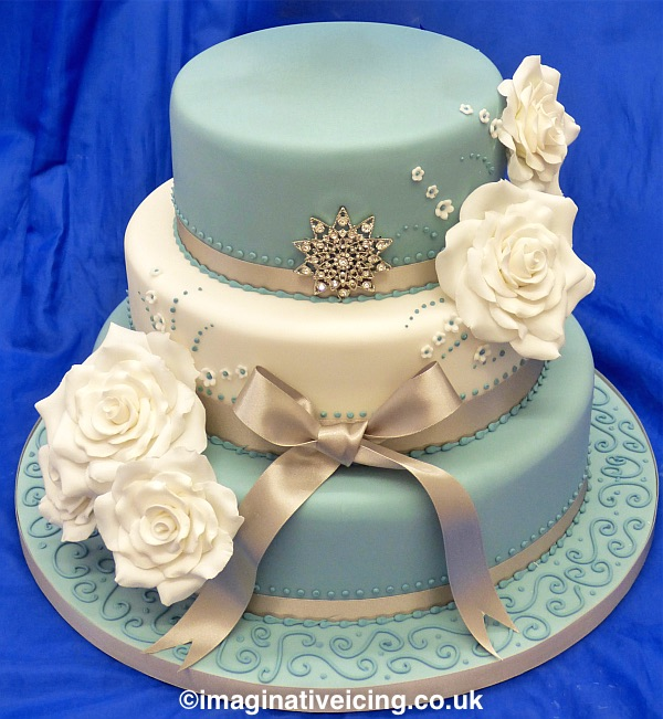 3 tier pearlised blue & ivory stacked Wedding Cake with sugar flowers satin ribbon and piped detail. Space on the top for a bride and groom cake topper or more flowers.
