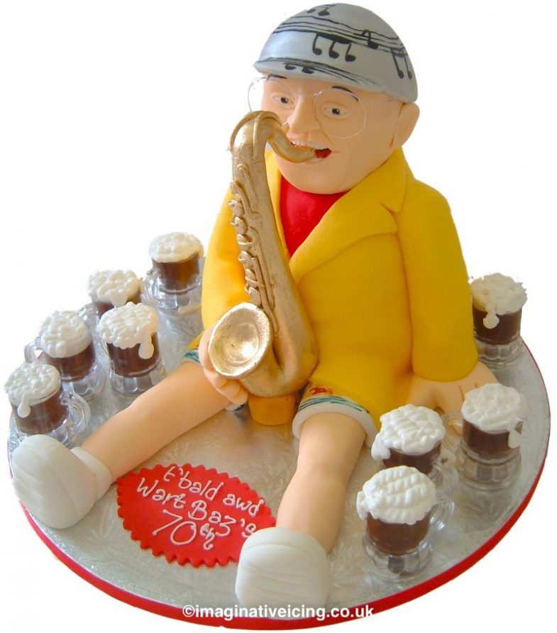 """3D Saxophone player Baz Hamps 70th Birthday Cake - cake shaped as the birthday person playing an icing saxophone and wearing a silver musicical note hat and bermuda shorts, red t-shirt and yellow jacket. White socks and trainers.. 7 pints of beer. Inscription """"t'bald awd wart Baz's 70th"""" piped in icing on red plaque on board."""