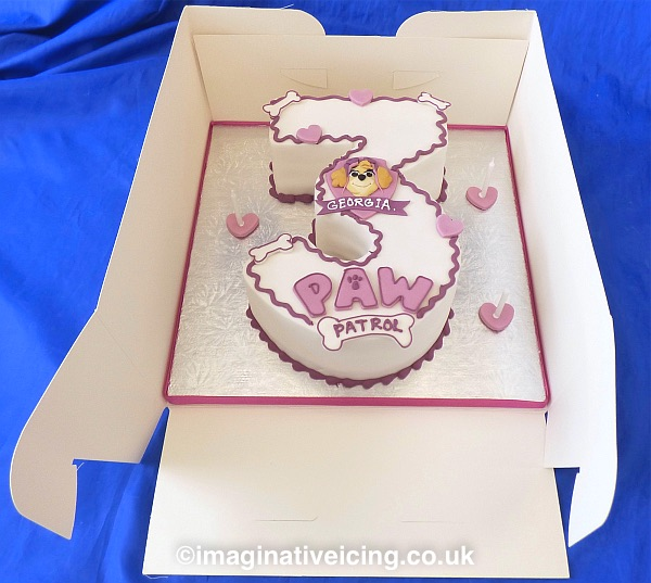 Children's 3rd birthday - shaped Number 3 cake on a silver board, ribbon and candles. Seen here in a white card box. Can be decorated to suit what your child is interested in at the time of ordering.