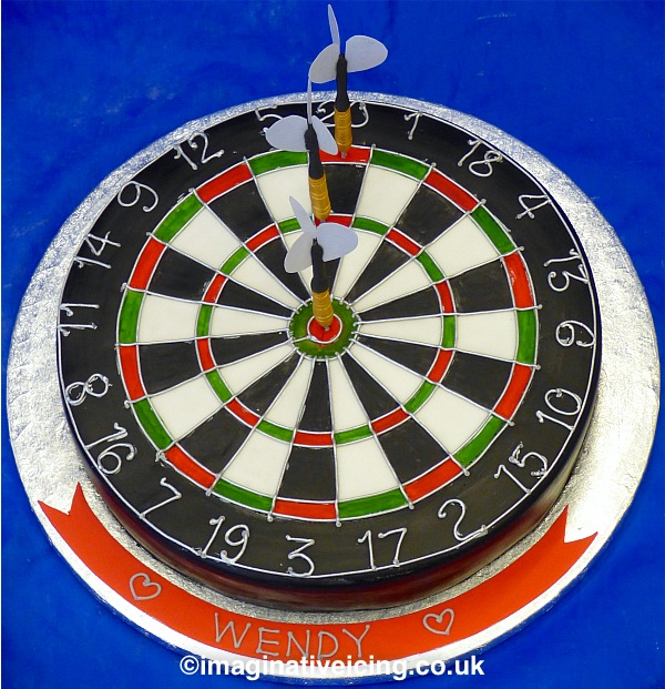 Dartboard Birthday Cake with 3 edible icing darts with flights, one in bulls eye others in treble and double top.  Piped icing silver detail with piped icing inscription. Candles can be added on the cakeboard round the base of the cake in icing holders.