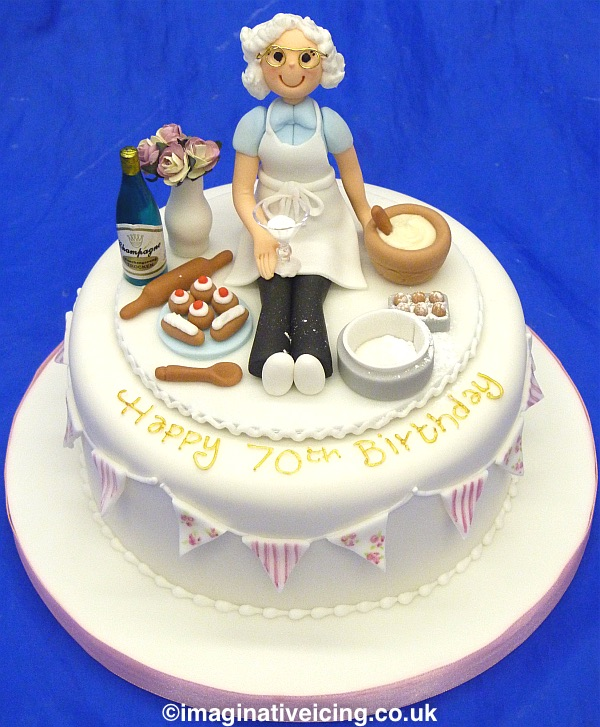Granny Baker Birthday Cake - with edible bunting round sides. Icing model of Granny wearing an apron sat down on the top of the cake surounded with her baking equipment, mixing bowl, wooden spoon, rolling pin, cake tin, eggs, champagne, flowers in a vase and a selection of iced buns on a plate. Hair style and colour can be done to match the birthday person.