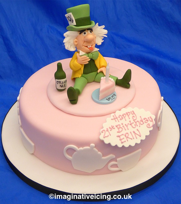The Mad Hatter sat adjusting his bow tie drinking and eating Alices' bottle of pop and slice of cake. White Cut out icing teapots, cups and saucers round the sides. Inscription piped in icing on an edible plaque attached to front of cake.