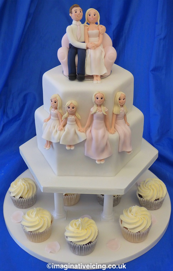 Mini 2 tier wedding cake with icing models of bride and groom sat cuddling on a sofa. Icing models of their 4 daughters sat on the edge of the second tier holding hands and dressed in pink and white dresses.  The cakes are raised on pillars above the cupcakes which have a swirl of vanilla buttercream in plain white paper cases which are on an iced cake board. Suitable for a small wedding with few guests.
