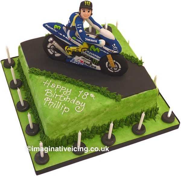 Motorcycle Motorbike Racing birthday cake - Icing model of a racing bike and rider wearing racing leathers and covered in sponsorship logos. Posing on bike with no helmet but wearing a cap. Square Cake iced to look like a country road race track with tarmac and green grass verges. candles on board. Happy Birthday Inscription piped in royal icing on top of cake.