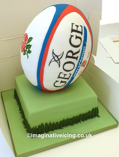 3D Rugby Ball shaped Birthday Cake with name of Birthday person in big on side and birthday inscription piped  below name. shown here standing on a base cake iced in green with some piped icing grass up the sides. space on cakeboard for some candles. Rugby ball can be decorated as appropriate to the birthday person's favourite rugby team.