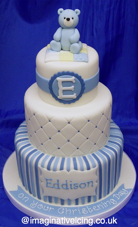 "3 tier Stacked Christening cake with blue icing teddy bear sat on a quilted blanket on top tier, Capital letter initial of baby's name on side of cake. Quilted emboss on the side of the second tier and pale and baby blue stripes on the base tier. Name piped on an icing plaque. ""on your Christening Day"" piped on an icing strip on the iced cake board. Ribbon round board."