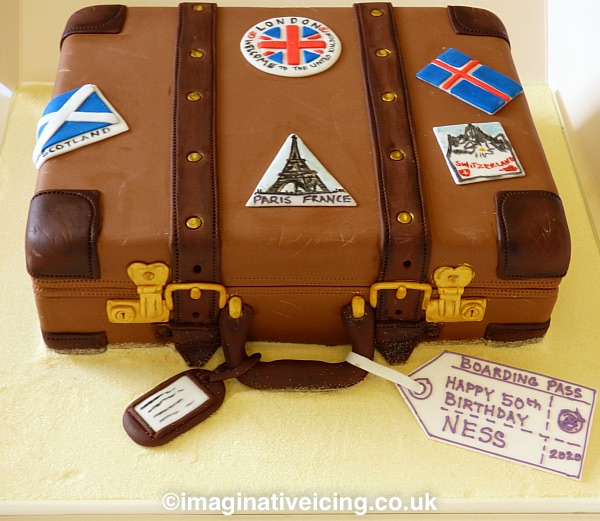 Vintage brown leather suitcase travel luggage cake with travel stickers and icing 50th birthday boarding pass tag. board iced to look like sandy beach. Marked with a few scuffs and scrapes from a lifetime of globe trotting. Stickers can reflect where the birthday traveller has been or is being taken in the future...